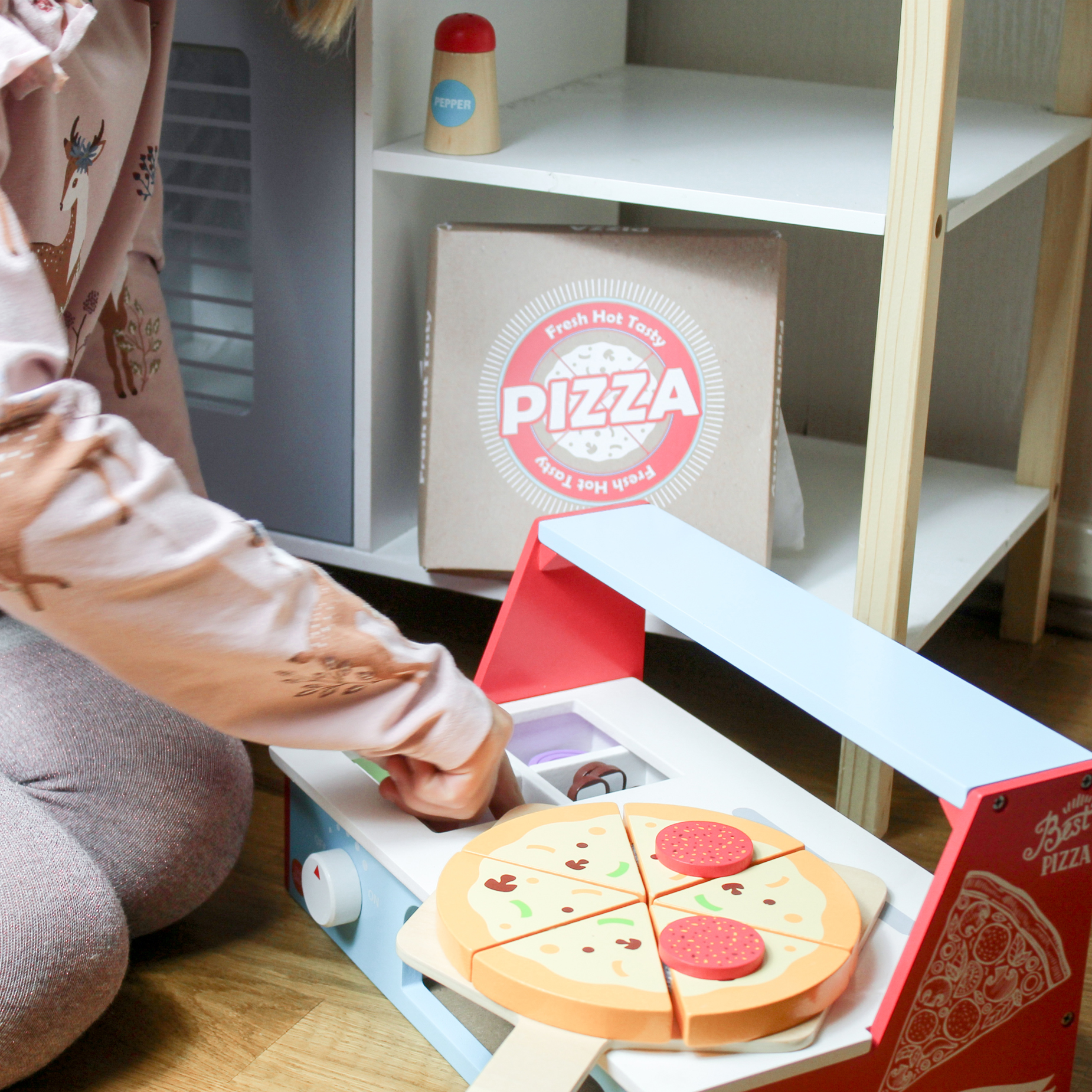 kid playing with wooden pizza base and wooden food/vegetables toy