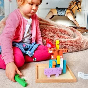 Little child playing with wooden animal toys