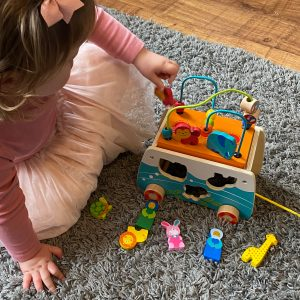 Kid playing with noah's ark shape sorter wooden toy