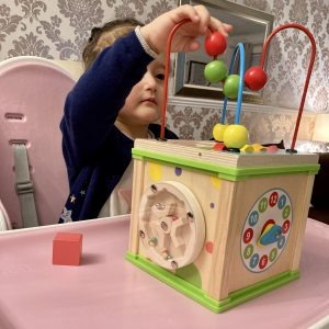 Little Girl Playing With Wooden Activity Cube