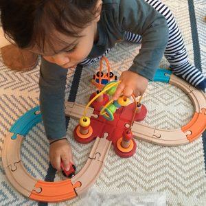 Kid Enjoying with Wooden Toy Train Railway Set