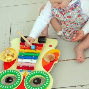 Kid playing Xylophone on wooden table