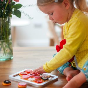 Little Girl Playing With Wooden Biscuit Baking Toy Set