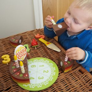 Toddler playing with Wooden Cake toy Set