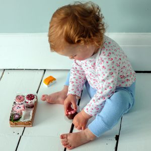 Little one playing with wooden biscuits and cakes