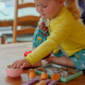 Toddler playing with wooden food set